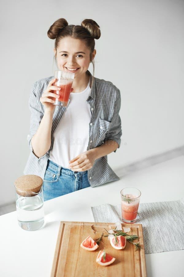 Belle fille avec le smoothie potable de sourire de detox de pamplemousse de petits pains à l'appareil-photo au-dessus du mur blan photo libre de droits