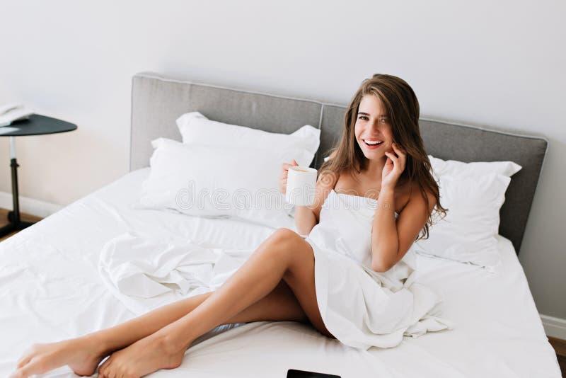 Belle fille avec les épaules et les jambes vilaines sur le lit blanc en appartement moderne Elle a de longs cheveux, tient la tas photos stock
