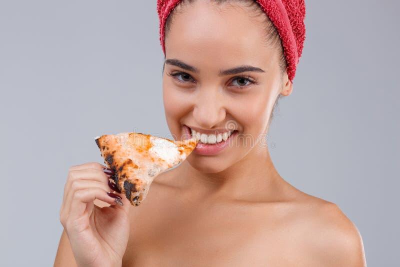 Belle fille, avec les épaules nues et avec une serviette sur son chef, mangeant appétissant une tranche de pizza photographie stock libre de droits