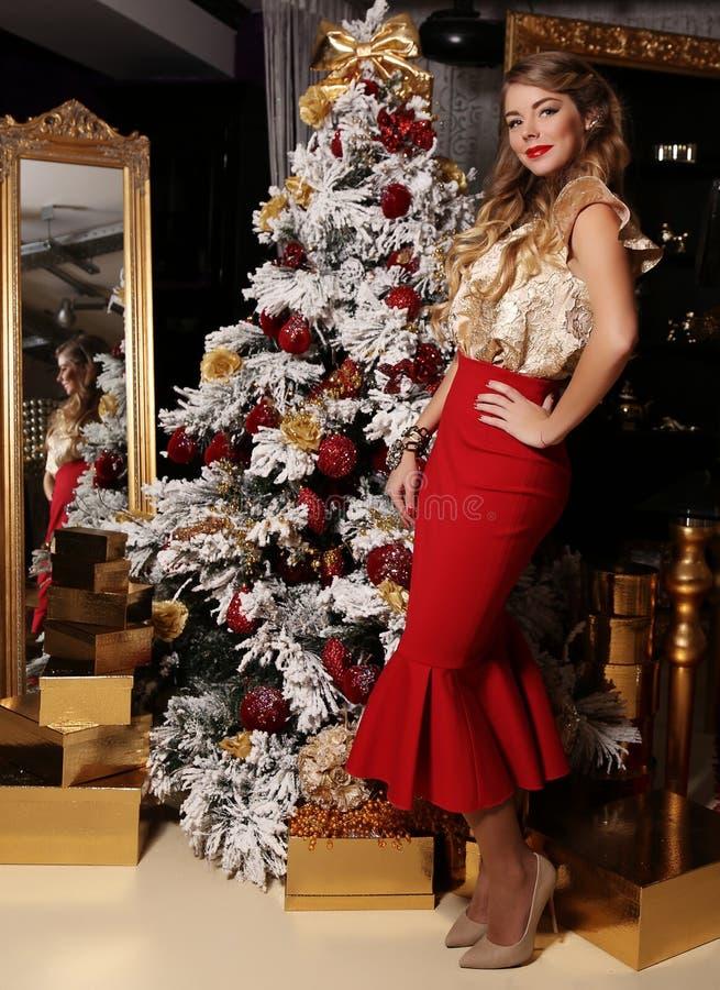 Belle fille avec les cheveux blonds, posant près de l'arbre de Noël photos stock