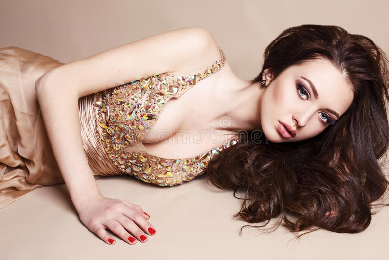 Belle fille avec les cheveux foncés dans la robe luxueuse de paillette photo libre de droits