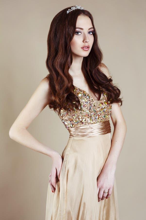 Belle fille avec les cheveux foncés luxueux dans la robe de paillette posant au studio photos libres de droits