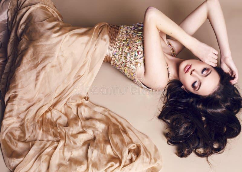 Belle fille avec les cheveux foncés luxueux dans la robe de paillette posant au studio photographie stock