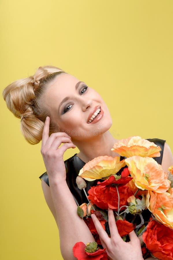 Belle fille avec les fleurs lumineuses dans des ses mains image stock