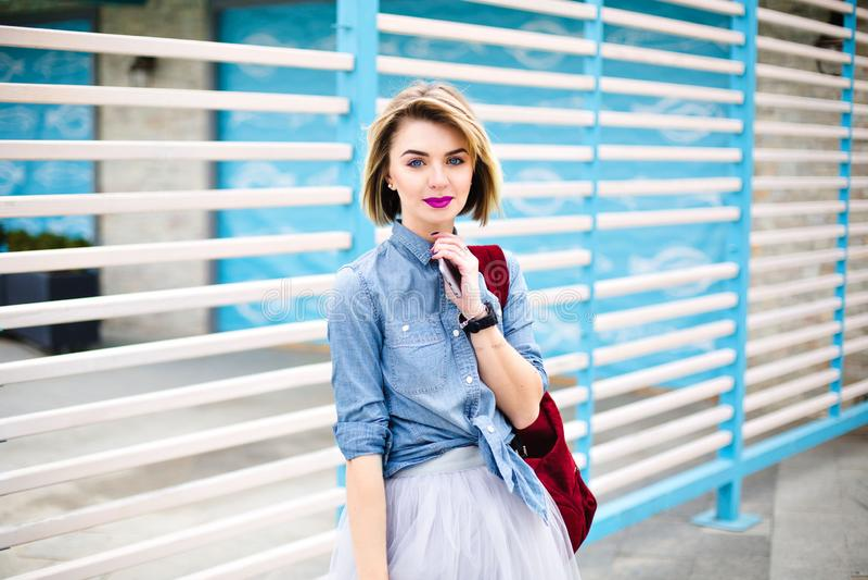 Belle fille avec les lèvres roses lumineuses et tatouage sur son smartphone de participation de main utilisant la chemise bleue d image stock