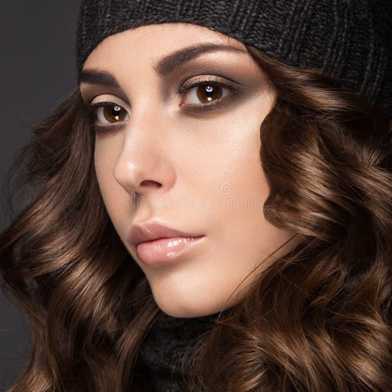 Belle fille avec Smokeymakeup, boucles dans le chapeau noir de knit Image chaude d'hiver Visage de beauté photos libres de droits