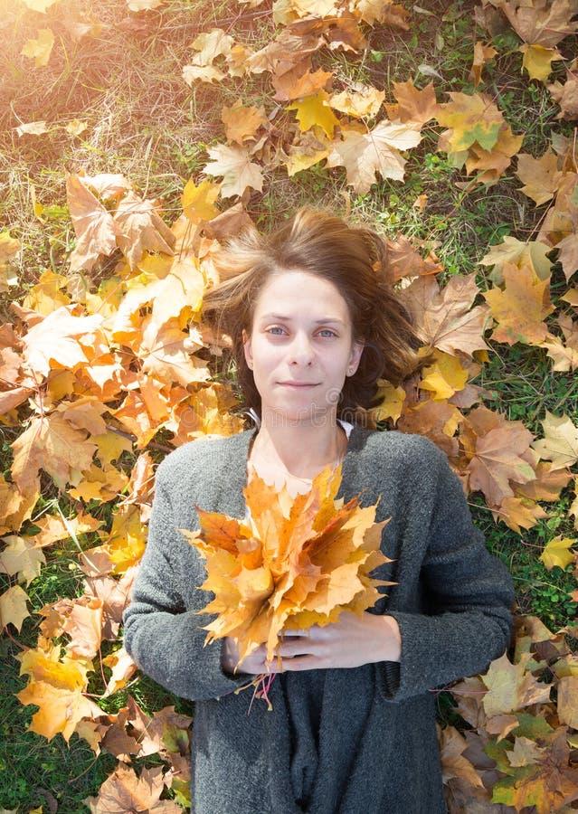 Belle fille avec un bouquet des feuilles en parc d'automne photographie stock libre de droits