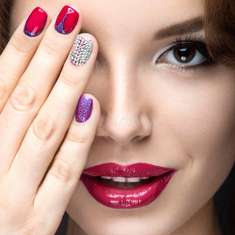 Belle fille avec un maquillage lumineux de soirée et manucure avec des fausses pierres Conception de clou Visage de beauté photo stock