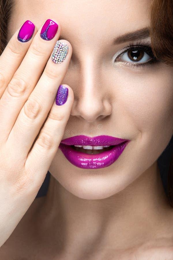 Belle fille avec un maquillage lumineux de soirée et manucure pourpre avec des fausses pierres Conception de clou Visage de beaut image libre de droits