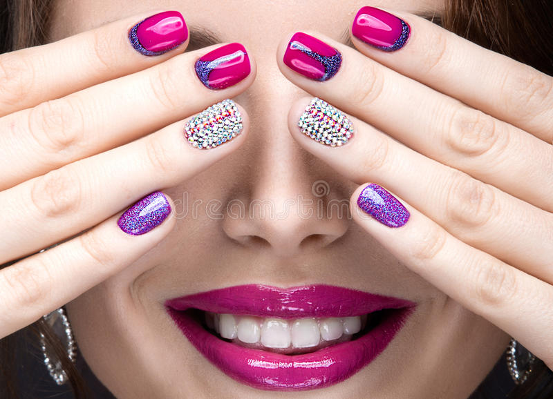 Belle fille avec un maquillage lumineux de soirée et manucure rose avec des fausses pierres Conception de clou Visage de beauté photos libres de droits