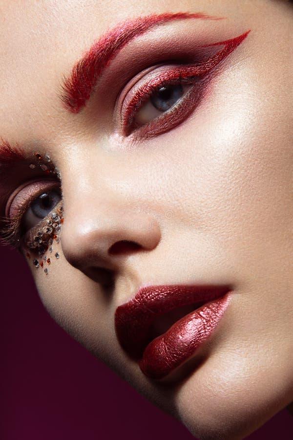 Belle fille avec un maquillage rouge lumineux de mode et cristaux sur le visage Portrait en gros plan image libre de droits