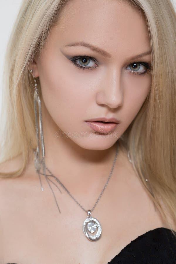 Belle fille avec un pendant argenté autour du sien photos stock