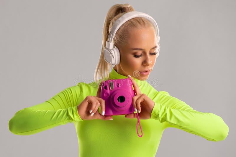 Belle fille avec une caméra, photographe de femme de mode dans des vêtements colorés, sur le fond gris photographie stock libre de droits