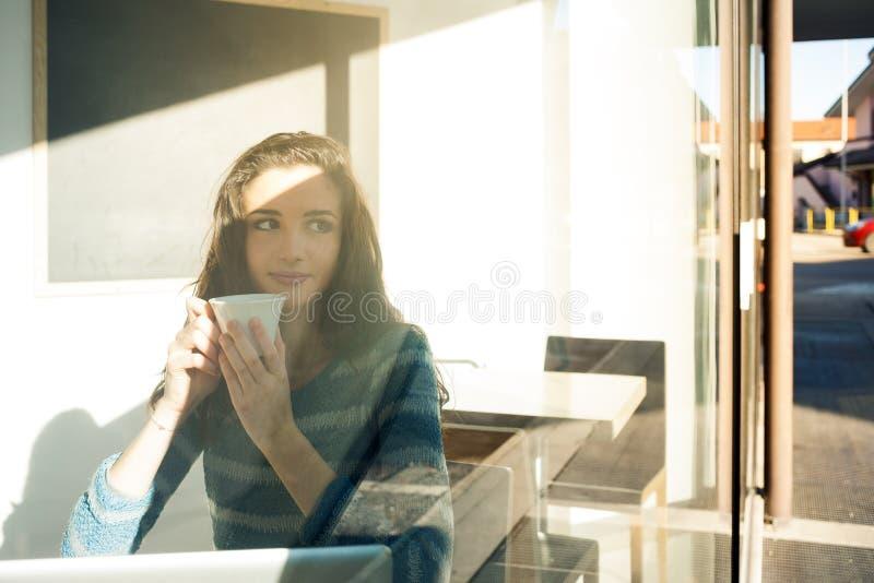 Belle fille ayant une pause-café à la barre image stock
