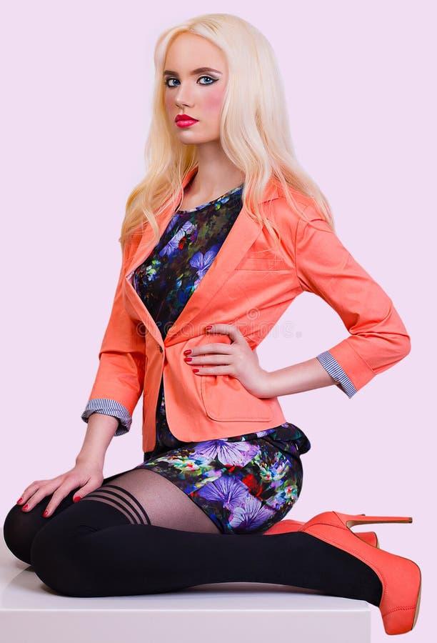 Belle fille blonde à la mode dans la veste orange photographie stock