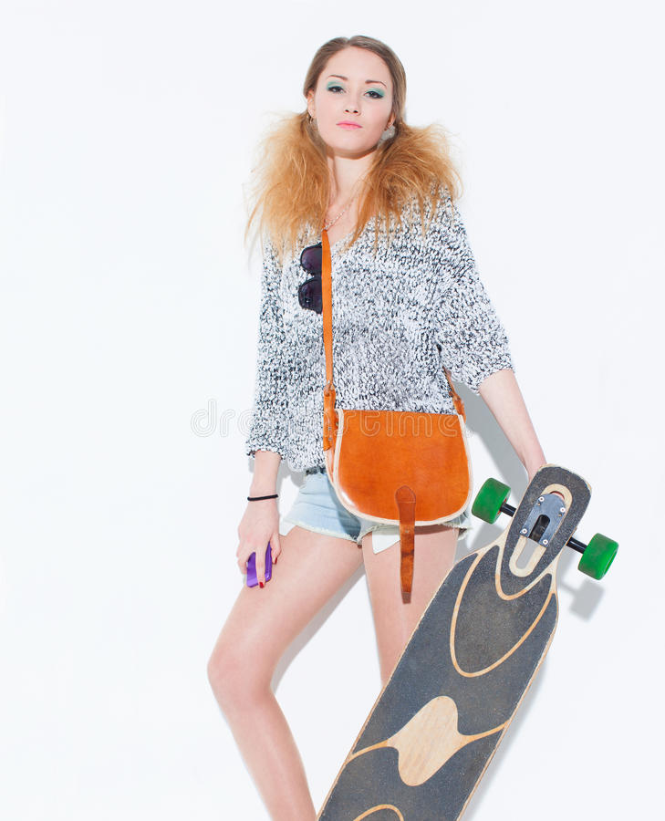 Belle fille blonde à la mode posant avec un visage hautain avec un sac de vintage sur l'épaule jugeant le longboard de main près  photo libre de droits