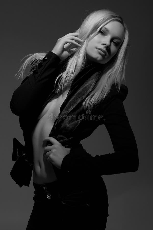 Belle fille blonde à moitié nue à la mode et sexy dans la pose noire de costume au fond foncé photo stock
