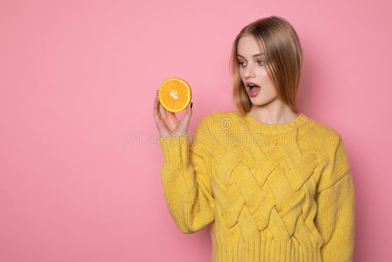 Belle fille blonde ?tonn?e dans le chandail jaune regardant le citron coup? en tranches images stock