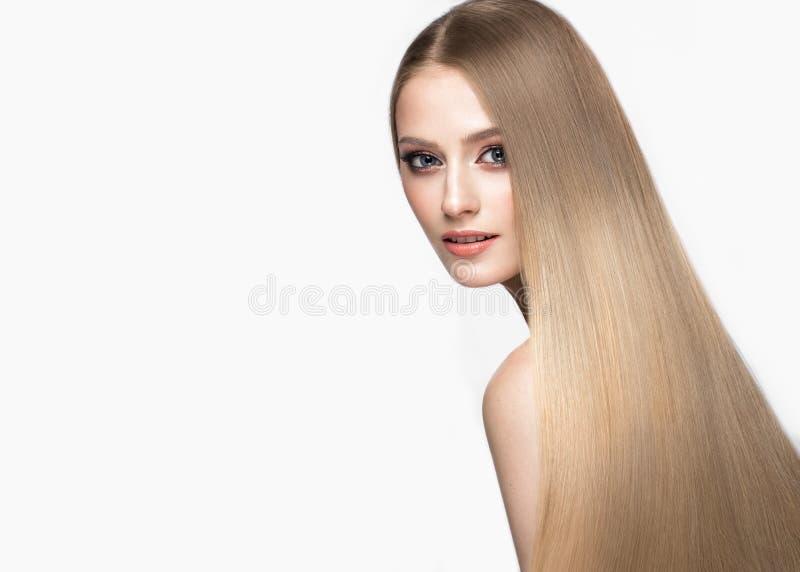 Belle fille blonde avec des cheveux parfaitement lisses, et maquillage classique Visage de beauté images stock