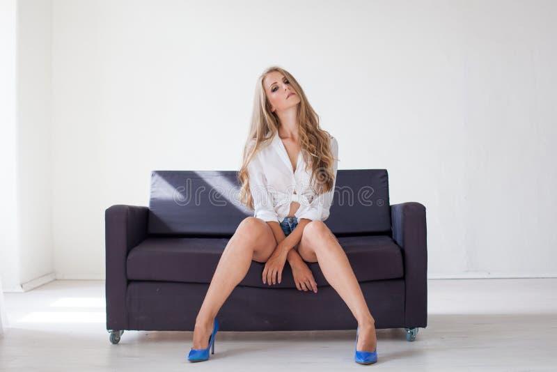 Belle fille blonde avec des yeux bleus se reposant sur le divan dans une salle blanche 1 photographie stock