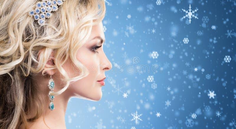 Belle fille blonde avec le collier d'or de luxe au-dessus du winte bleu photos libres de droits