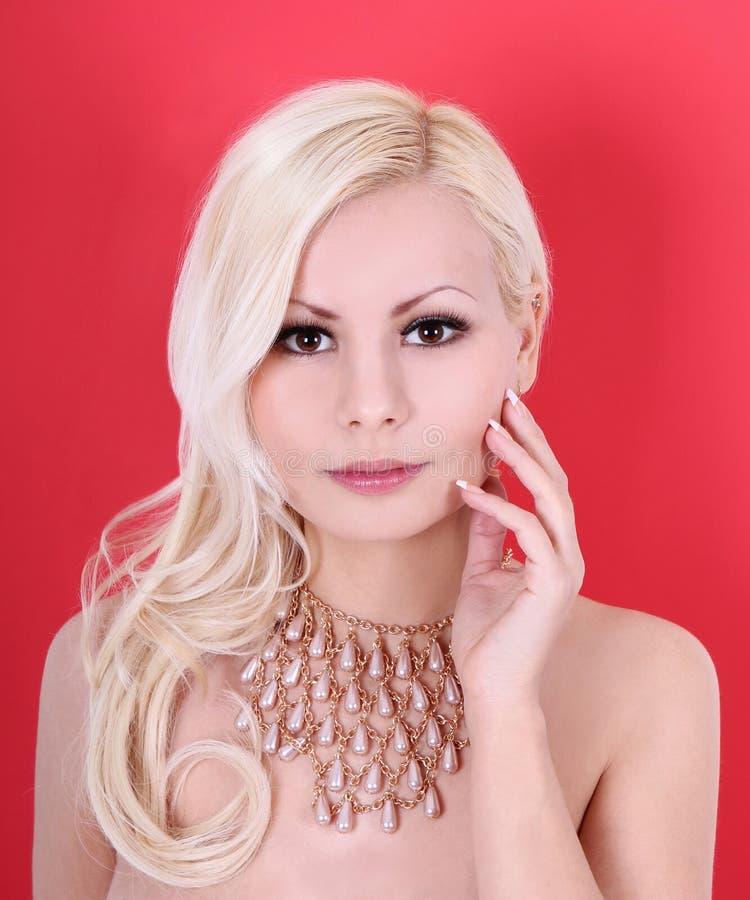 belle fille blonde avec le collier de perle sur le rouge image stock