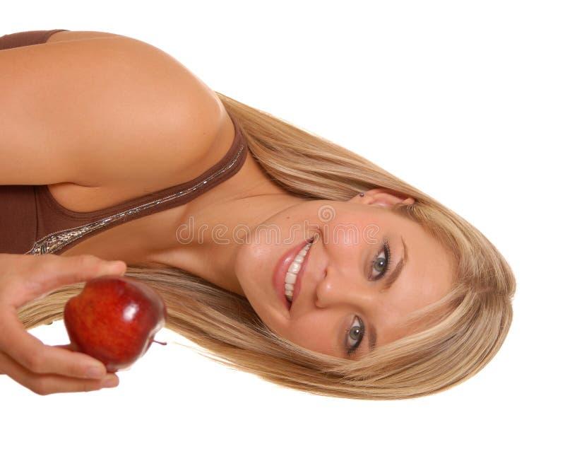 Belle fille blonde avec une pomme photographie stock