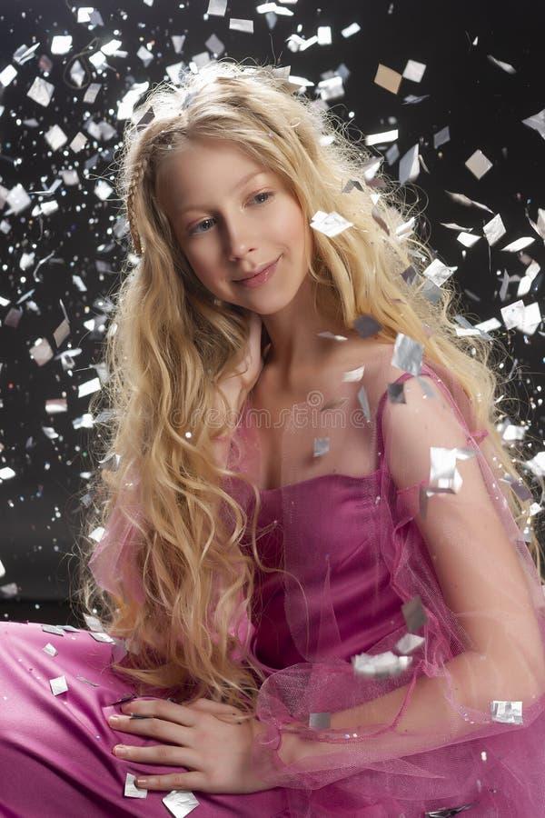 Belle fille blonde bouclée d'enfant d'adolescent portant un Dr. rose d'air photographie stock libre de droits