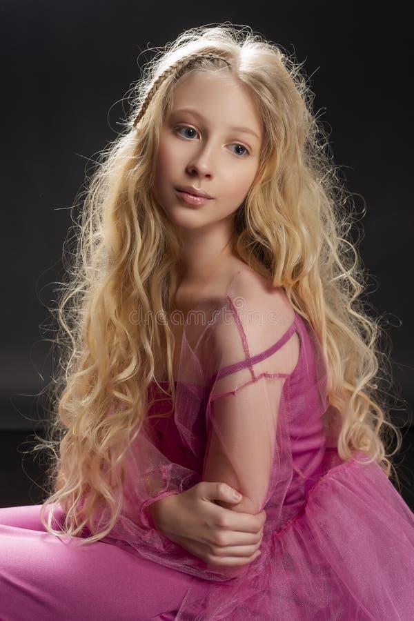 Belle fille blonde bouclée d'enfant d'adolescent portant un Dr. rose d'air photos stock
