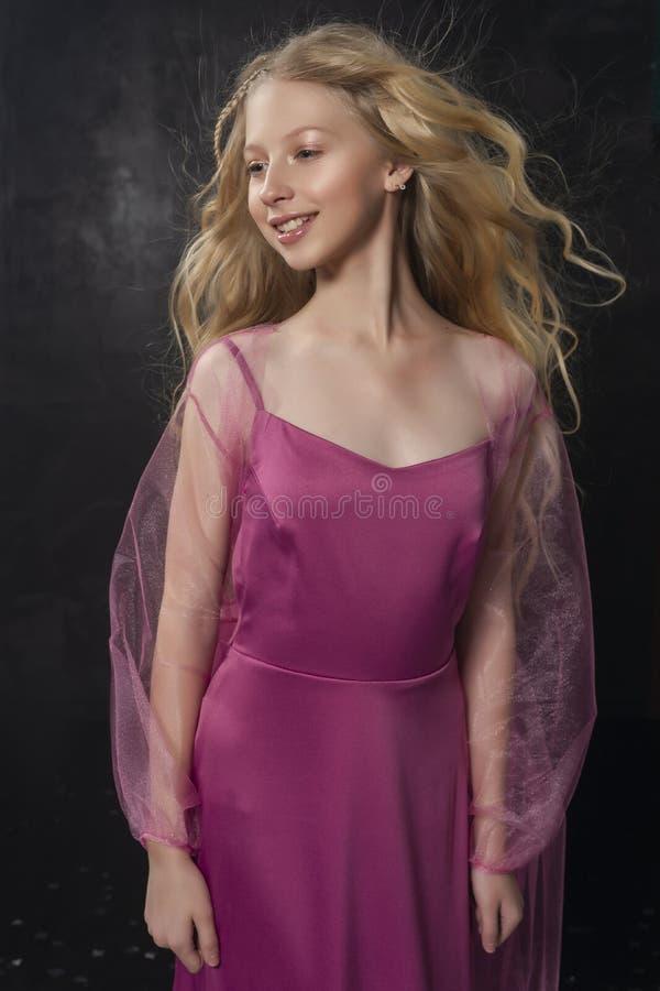 Belle fille blonde bouclée d'enfant d'adolescent portant un Dr. rose d'air photos libres de droits
