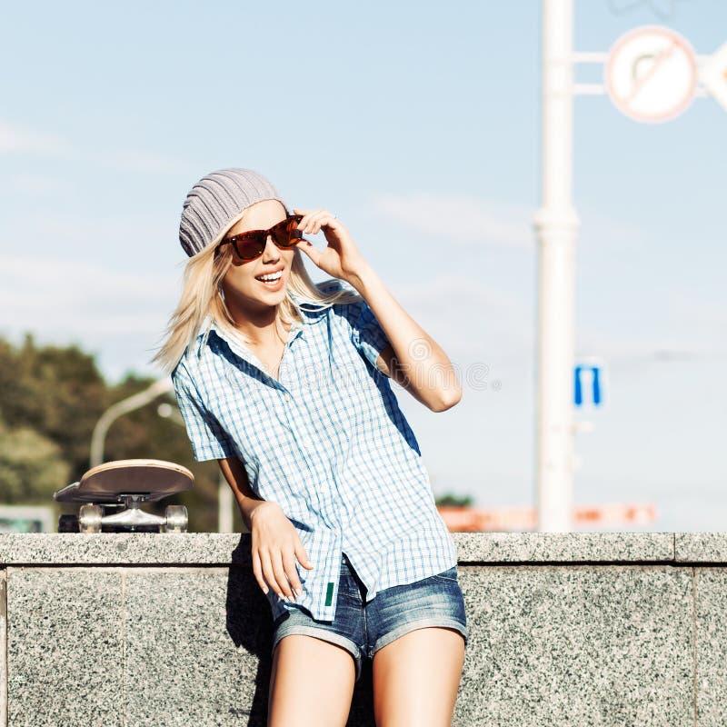 Belle fille blonde dans des shorts courts avec la planche à roulettes photographie stock