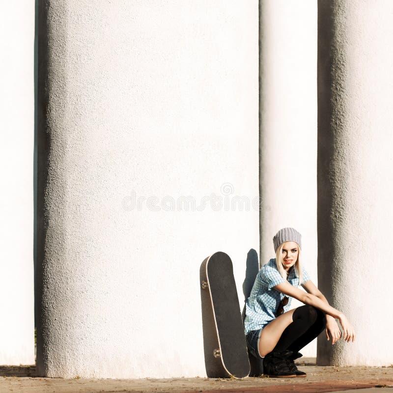 Belle fille blonde dans des shorts courts avec la planche à roulettes photographie stock libre de droits