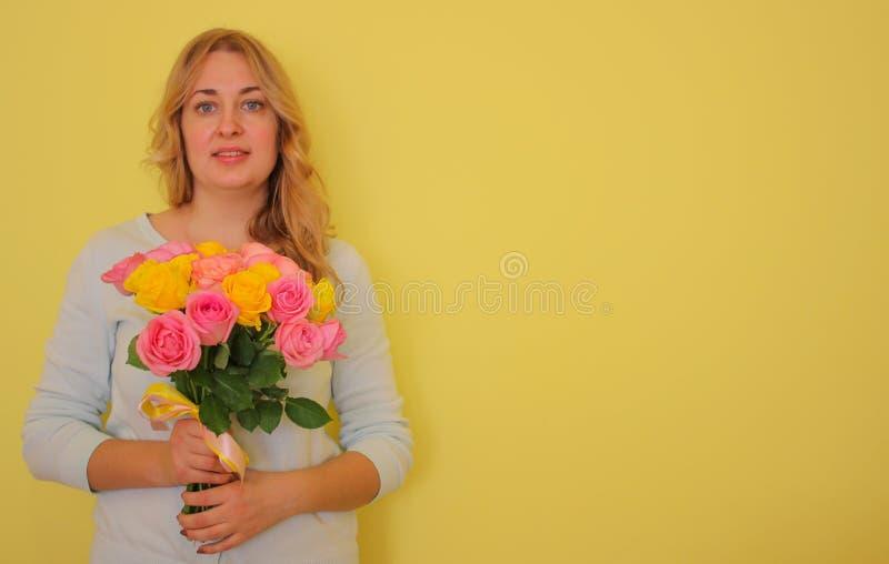 Belle fille blonde dans le bouquet bleu de participation de robe des roses jaunes et roses sur un fond jaune-clair photos libres de droits