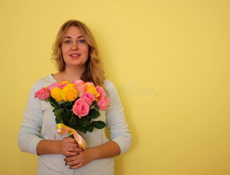 Belle fille blonde dans le bouquet bleu de participation de robe des roses jaunes et roses sur un fond jaune-clair photo stock