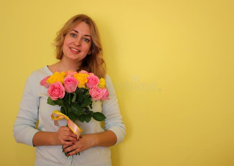 Belle fille blonde dans le bouquet bleu de participation de robe des roses jaunes et roses sur un fond jaune-clair photographie stock