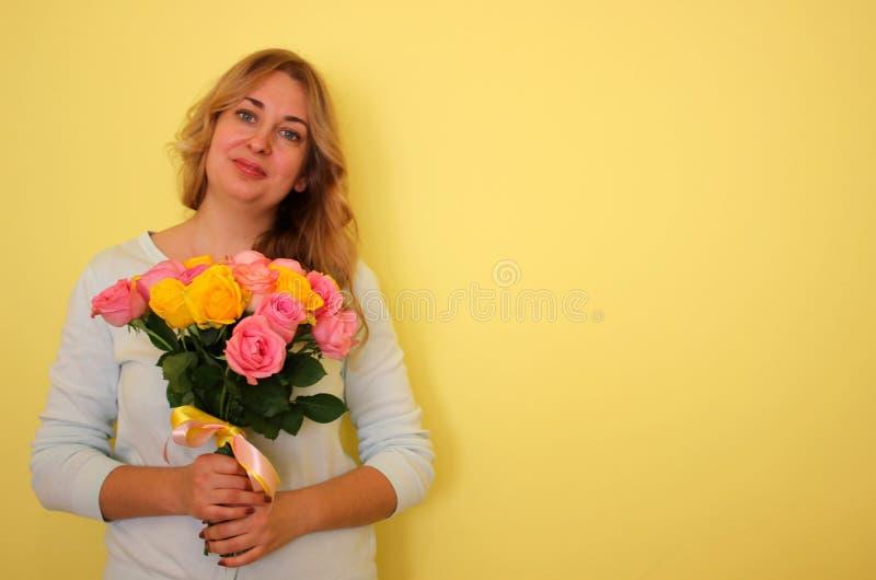 Belle fille blonde dans le bouquet bleu de participation de robe des roses jaunes et roses sur un fond jaune-clair images libres de droits