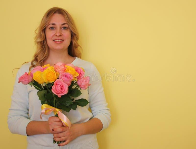 Belle fille blonde dans le bouquet bleu de participation de robe des roses jaunes et roses sur un fond jaune-clair photographie stock libre de droits