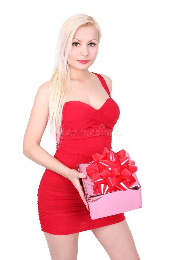Belle fille blonde dans le cadre de cadeau rouge de fixation de robe images stock