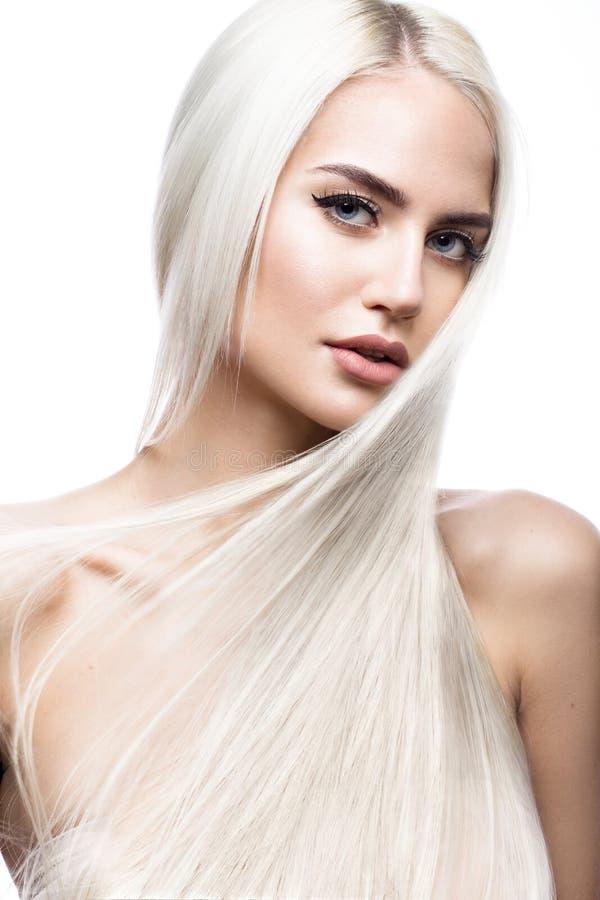 Belle fille blonde dans le mouvement avec des cheveux parfaitement lisses, et maquillage classique Visage de beauté image stock
