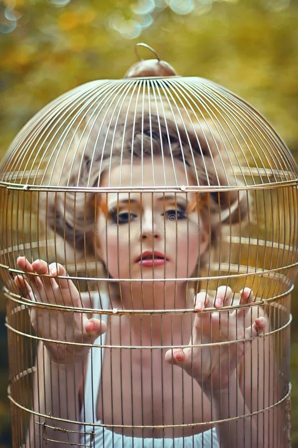 Belle fille blonde dans une cage d'or photo libre de droits