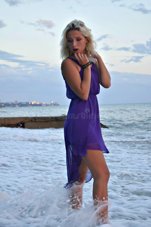 Belle fille blonde dans une robe légère sur le rivage de la mer préoccupée photographie stock
