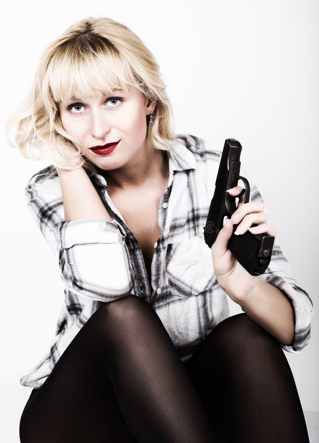 Belle fille blonde de portrait en gros plan avec les lèvres rouges utilisant une chemise de plaid, tenant une arme à feu photo libre de droits