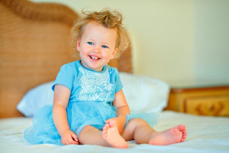 Belle fille blonde heureuse d'enfant en bas âge s'asseyant sur un lit photos libres de droits