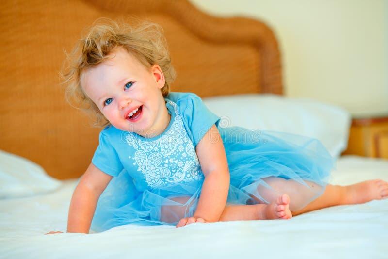 Belle fille blonde heureuse d'enfant en bas ?ge s'asseyant sur un lit photo stock