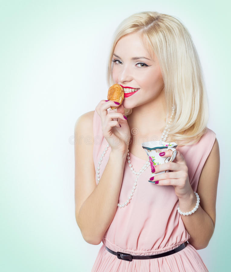 Belle fille blonde magnifique sexy avec le maquillage lumineux dans la robe rose dans le studio sur une séance blanche de fond photographie stock libre de droits