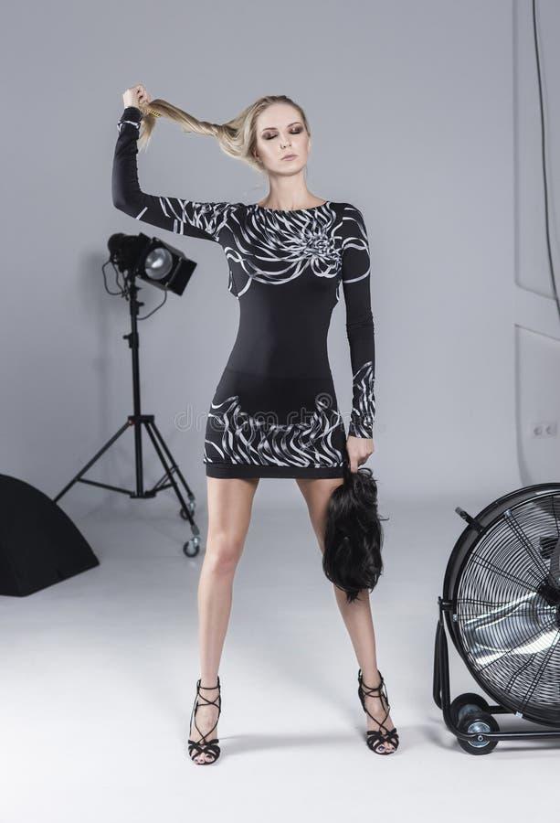Belle fille blonde mince aux longues jambes habillée dans une robe convenable foncée courte posant sur un fond blanc de aux lampe image stock