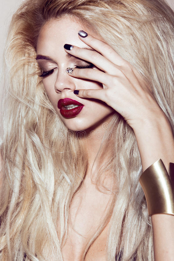 Belle fille blonde sexy avec les lèvres sensuelles, cheveux de mode, ongles d'art noir Visage de beauté photographie stock libre de droits