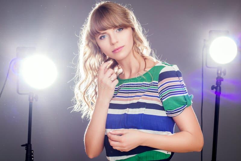 Belle fille bouclée blonde se préparant au photosession image stock