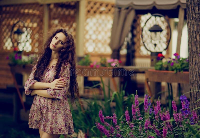 Belle fille bouclée de brune sur le fond de lattic en bois images libres de droits