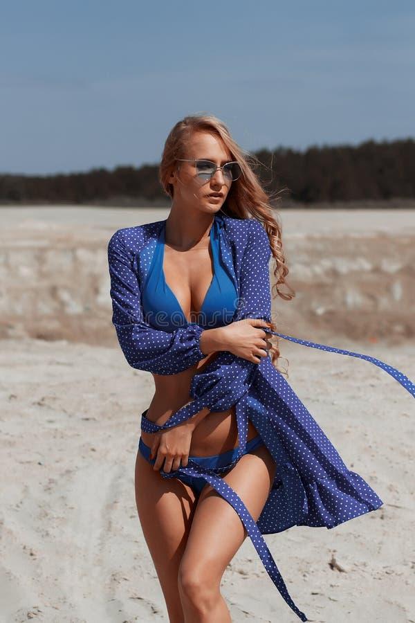 Belle fille bronz?e se trouvant sur le sable V?tements de bain de port de charme de fille attirante sur la plage tropicale tout e photo libre de droits